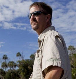 photo of Tom Frazer in the field with blue skies and palm trees in the background